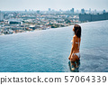 Young beautiful woman relax in swimming pool on rooftop and enjoy cityscape 57064339