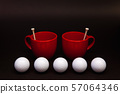 White golf balls and red cups of tea on the black 57064346