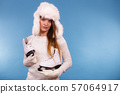 Woman wearing winter hat holding ice skate 57064917