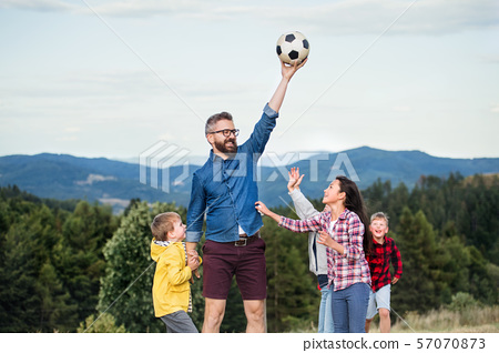 Group of school children with teacher on field trip in nature, playing with a ball. 57070873