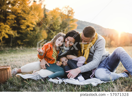 A portrait of young family with two small children in autumn nature at sunset. 57071328
