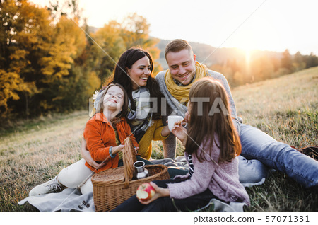 A young family with two small children having picnic in autumn nature at sunset. 57071331