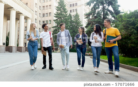 Happy students walking outside the university building 57071666