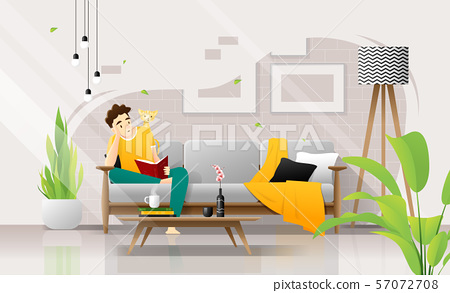 Happy young man sitting on sofa and reading a book in living room, relaxing weekend at home 57072708