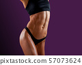 Beautiful super fit young woman showing off her 57073624