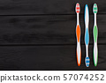 Colorful toothbrushes on black wooden background. 57074252
