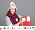 Young Beautiful Woman in winter clothes showing 57077370