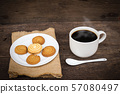 Cup of coffee on sackcloth napkin, on wooden table 57080497