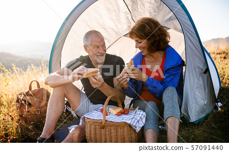 Senior tourist couple sitting in nature at sunset, eating sandwiches. 57091440
