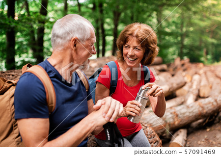 Senior tourist couple with flask on a walk in forest in nature, sitting. 57091469
