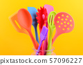 bright multi colored kitchen utensils on yellow background 57096227