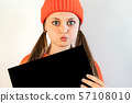 A beautiful girl in a red hat with large wide open eyes holds a black sheet  57108010