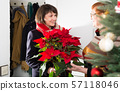 Woman visiting her mother with poinsettia 57118046