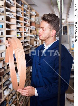 Working man examining edging strips to finish work 57118344