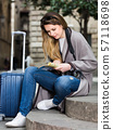 traveling girl searching for the direction using a booklet in the town 57118698