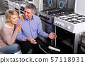 Husband and wife in store select to gas stove 57118931
