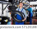 worker holding new tyre 57120188