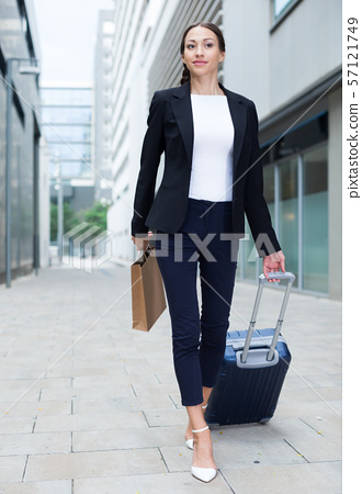 Successful adult businesswoman in suit with suitcase is going to the hotel 57121749