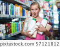 Happy girl holding shampoo and shower gel 57121812