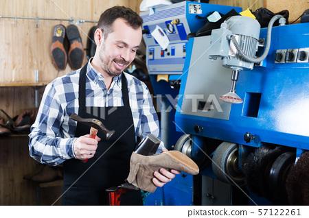 Male worker repairing shoe 57122261