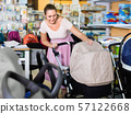 Pregnant woman buying baby stroller in kids mall 57122668