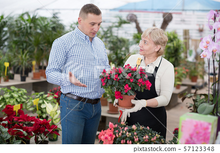 Adult woman is helping to man with choice of blooming flower 57123348