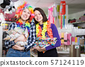Cheerful female friends with bags of confetti 57124119