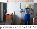 Worker is working with level near the wall at the object indoors. 57124159