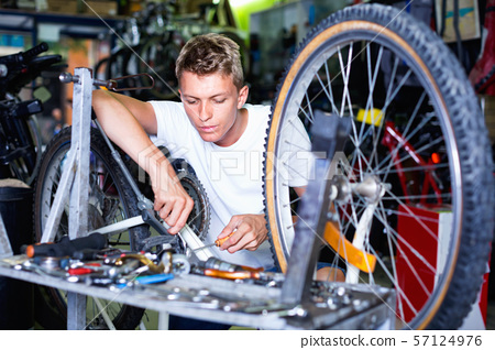 Man repairing bicycles with instruments indoors 57124976