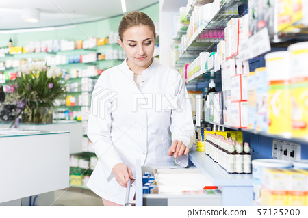 druggist is searching medicine in drawers 57125200