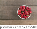 Strawberries in white bowl on wood table 57125589