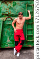 portrait of shirtless man standing against wall 57126750