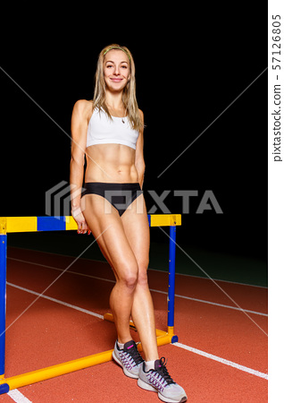 Young athletic woman standing at the hurdle 57126805