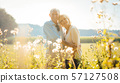 Senior couple on a sunlit meadow embracing each other 57127508
