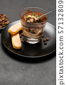 Portion of Classic tiramisu dessert in a glass cup on dark concrete background 57132809