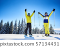Happy couple skiers standing on mountain edge, rejoicing, raising hands up. Clear blue sky over 57134431