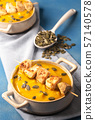 Pumpkin cream soup bowls with chicken skewers. 57140578