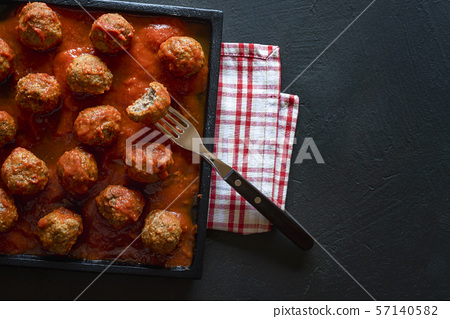 Meatballs in tomato sauce on black tray. Above 57140582