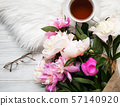 Cup of tea and pink peonies 57140920