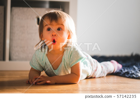 Adorable baby girl lying down on the carpet with funny expression 57142235