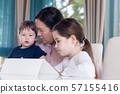 Grandma entertaining her little grandchildren with a tablet computer game 57155416