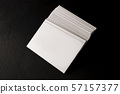 A mock-up of a stack of white business cards on a black slate background 57157377