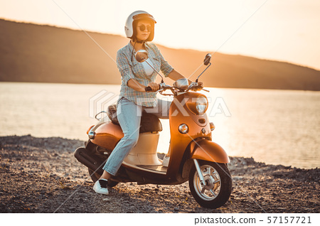 Woman in helmet sitting on red retro scooter.Cinematic vintage toned. Copy space 57157721