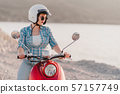Girl's portrait.Lady in colorful cloth and sunglasses sitting on red retro moped 57157749
