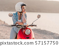 Young woman's portrait. Girl in helmet, eyeglasses sitting on red retro scooter 57157750