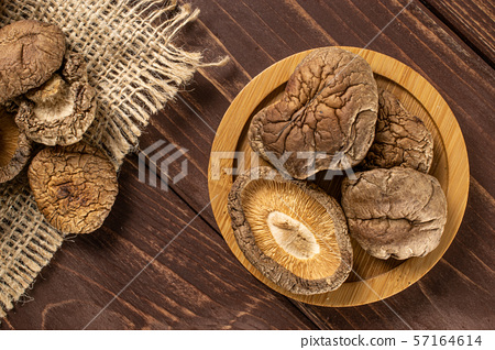 Dry shiitake mushroom on brown wood 57164614