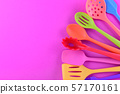 bright multi colored kitchen utensils on purple background with copy space 57170161