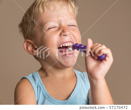 Little child smiling and brushing  her teeth 57170472