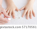 mother paints her child's nails with special nail polish by chewing finger nails 57170561