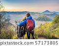 Young couple man and woman meet the sunrise at the Bromo Tengger Semeru National Park on the Java 57173805